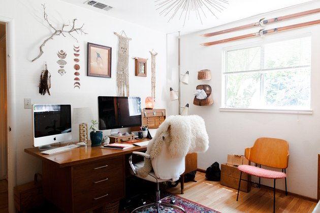 Home office with vintage wood desk, boho wall decor, and nearby window