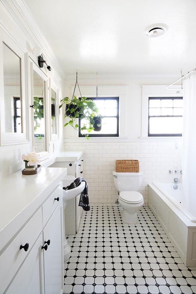 Salle de bain aux murs blancs avec carrelage blanc-noir