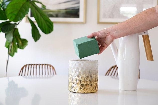 Main mettant un bloc d'oasis floral vert dans un vase texturé or-blanc