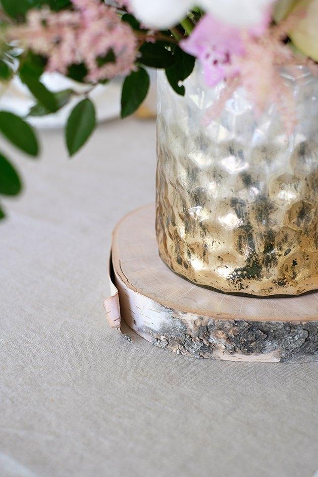Vase texturé blanc doré sur dessous de verre en bois sur table