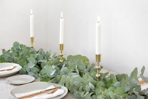a table runner made from bunches of eucalyptus branches studded with tapers