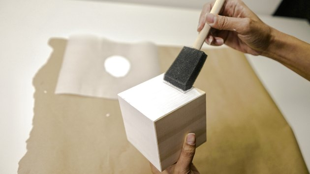 applying white paint to a block of wood with a foam brush