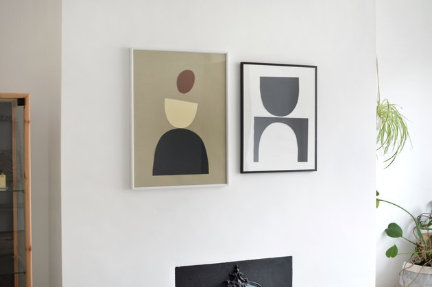Two framed DIY graphic art pieces on white wall in room with plants and wood-framed glass cabinet