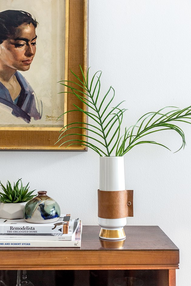 a vase with a decorative diy leather wrap sitting on a tabletop and filled with greenery