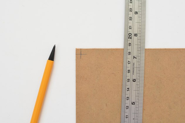 Metal ruler laying flat on top of cardboard panel next to mechanical pencil against a white background