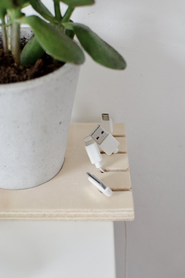 close-up on a cable organizer made out of a square of plywood with cables hanging from it and a potted plant inset