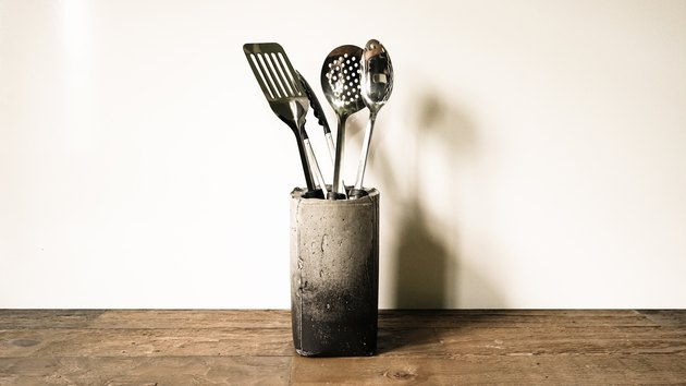Concrete vase with utensils on wood countertop