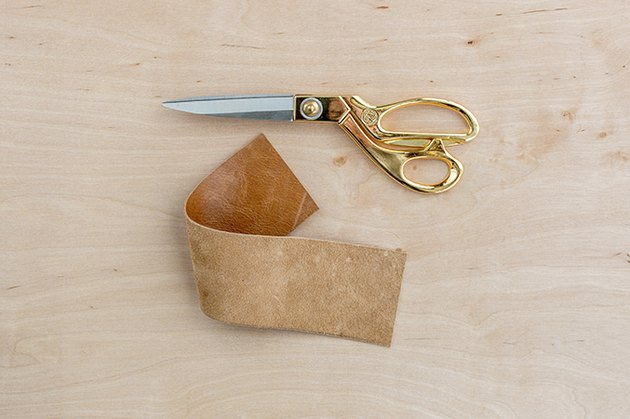 a wide strip of leather and scissors