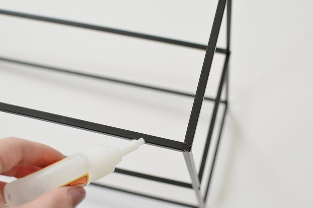 Hand applying Gorilla Glue to a black metal shelving frame against a white background