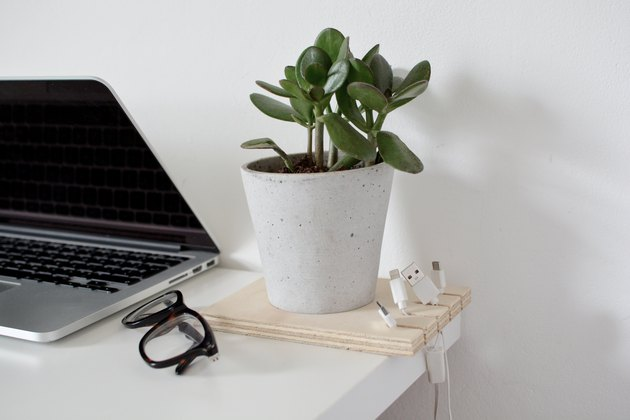 a cable organizer made out of a square of plywood with cables hanging from it and a potted plant inset