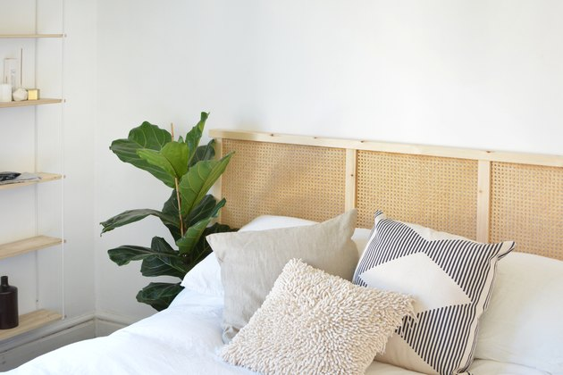 White bedding with assorted pillows and cane headboard in white room with plant and wood shelving