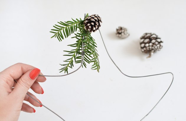 Star-shaped wire wreath with wintergreens and pinecones