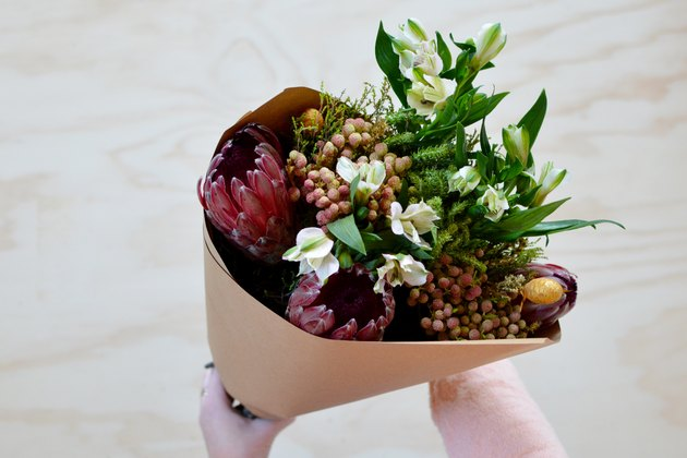 Hands holding bouquet with white, pink, red and yellow flowers with green leaves wrapped in brown paper against a light wood background