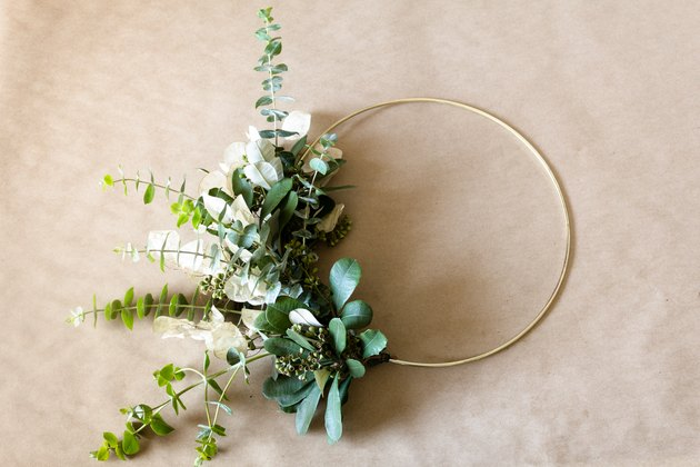 DIY Christmas decorations with bunches of greenery and white seed pods attached to a wire hoop