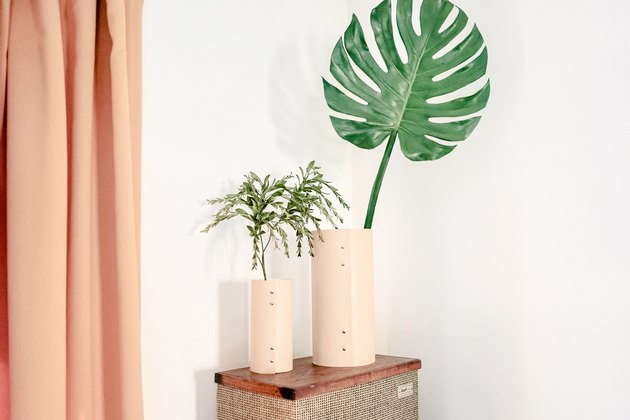 Beige leather vases with plants on side table next to peach curtains