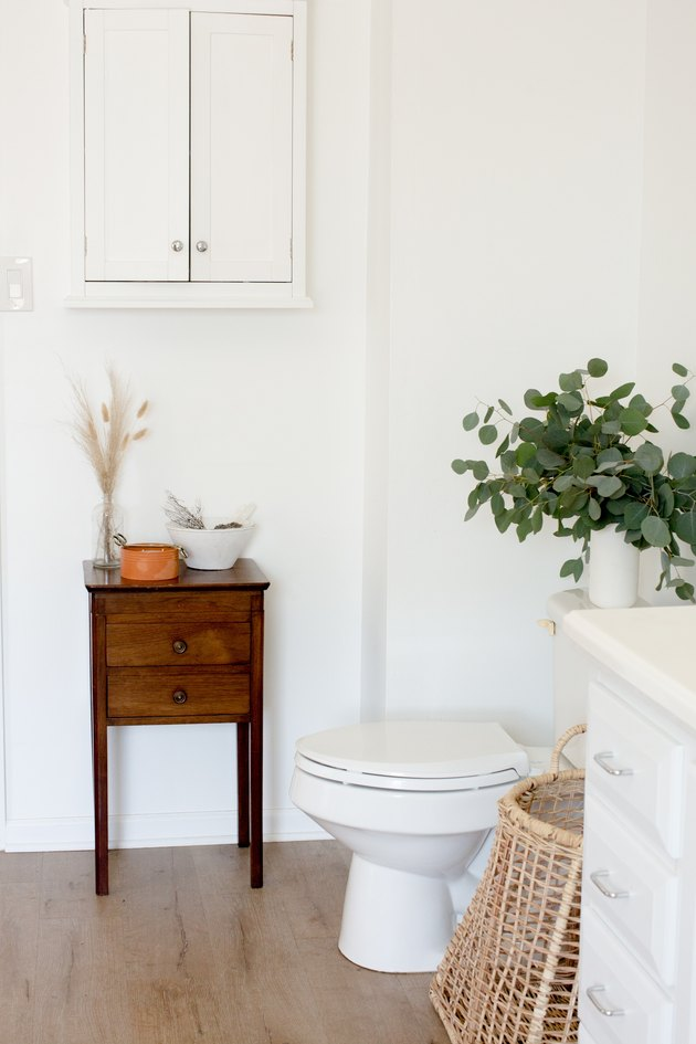 white toilet, small side table with drawers, rattan basket, vase filled with eucalyptus, white wall-hung cabinet, wood flooring, white bathroom vanity