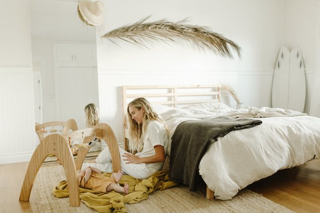 Woman sitting in white boho master bedroom with large wooden children's toys on the floor