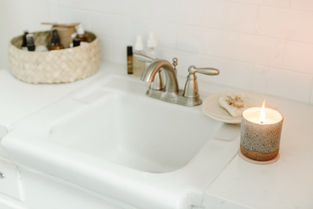 white sink, silver faucet, lit candle, basket full of various bathroom products