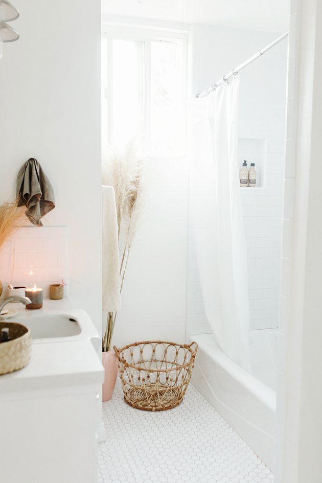 White bathroom with shower and wicker basket on floor