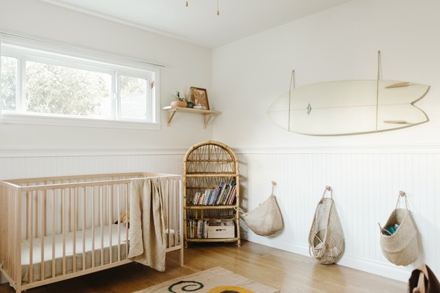 Neutral wood and white wainscoting nursery with white surfboard and baskets hanging on walls