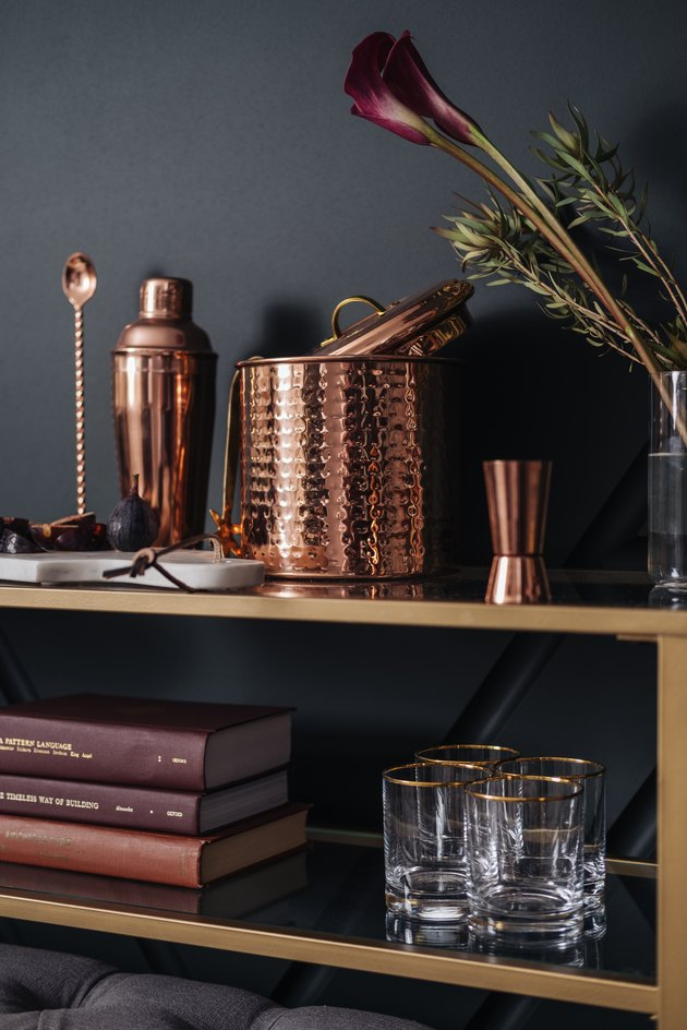 Shelving with books and glassware with copper cocktail set and flowers