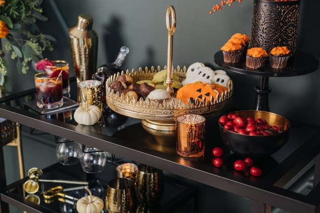 fall party idea with bar cart and gold cocktail set and cake stand with halloween cookies