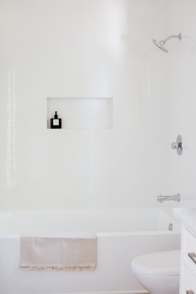 Bathroom with white walls, white tub, white toilet.