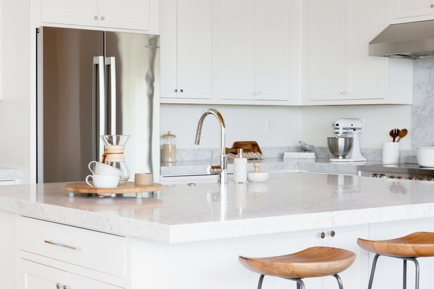 White kitchen island with a marble countertop. Two bar stools with wooden seats and metal legs in fron of it. On the countertop, two white mugs and a chemex, along with a sink with a chrome faucet. Behind the island, a stainless steel fridge and white cabinets.