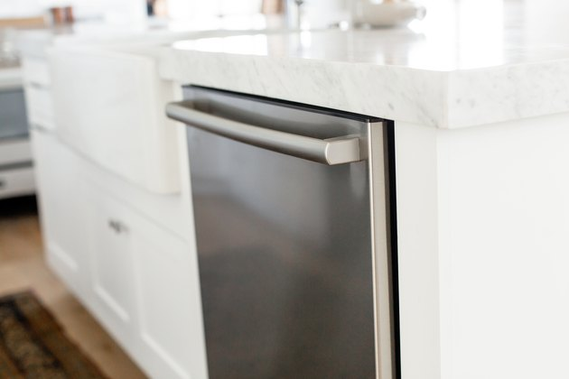 Stainless steel dishwasher in a white kitchen island. The marble countertop extends over the dishwasher.