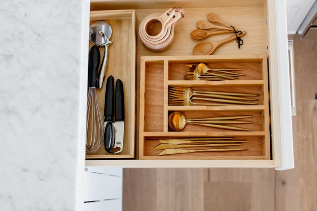 An open drawer with a wooden cutlery organizer. Gold cutlery, measuring cups and spoons, and other utensils visible inside. Marble countertop above the drawer.