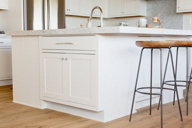 A row of bar stools with wooden seats and black metal legs in front of a white kitchen island with a marble countertop. Visible on the countertop is a chrome faucet, two stacked white mugs, and a Chemex.
