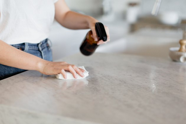 Shot of the midsection and hands of a woman in a white t-shirt and jeans. She's wiping down a kitchen counter with a brown glass spray bottle in one hand and a white rag in the other.