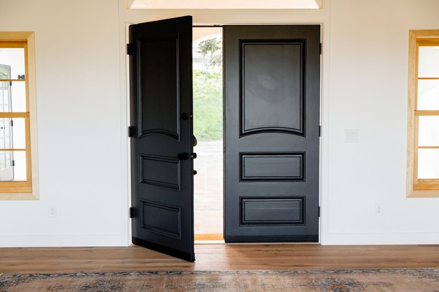 Black Room Ideas with Double doors made of dark wood, the main entrance to the home. Two windows with light wood frames, one on either side of the door.