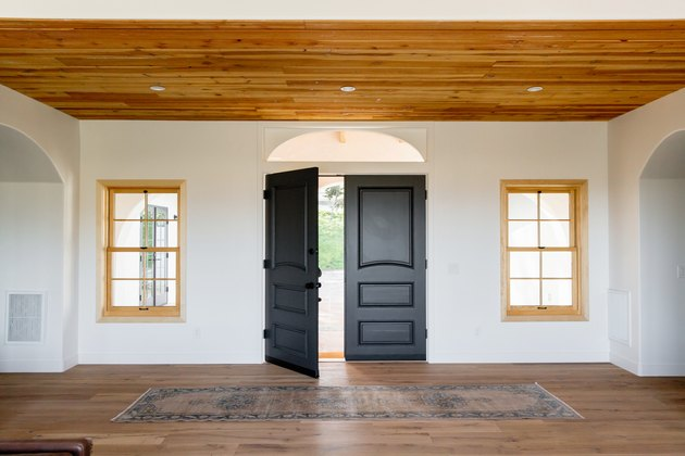 eco-friendly home design with an entry hall of a Spanish-style home with double dark wood doors, one of which is open, on a white wall. Two windows with light wood frames on either side of the door. The floor and ceiling are both made of wood. There's a rug in front of the door.