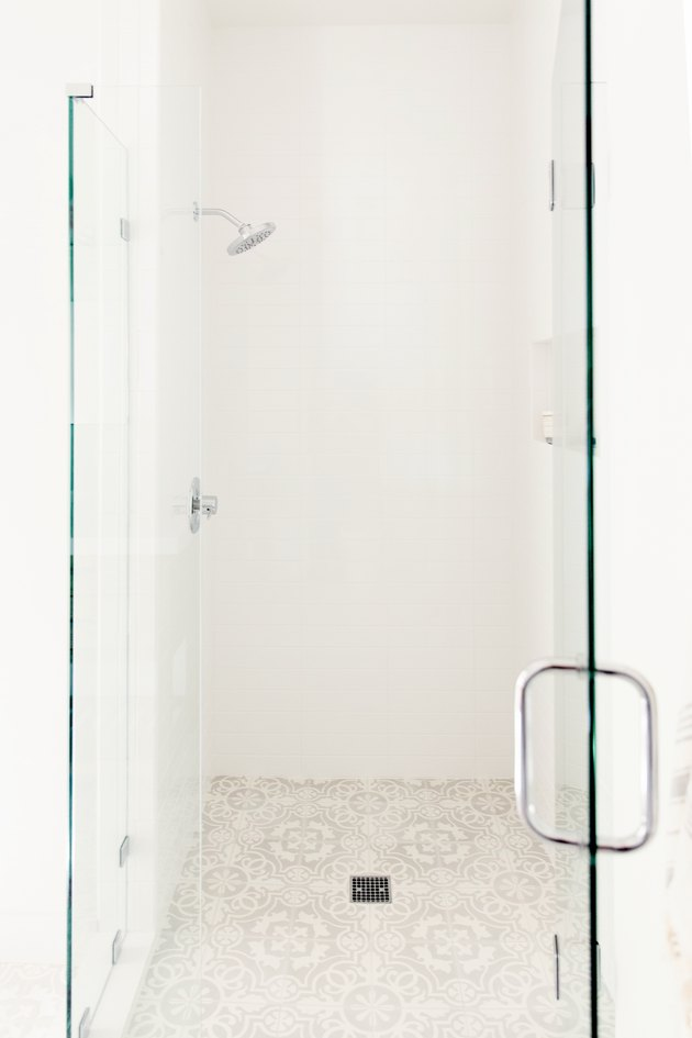A glass shower door with a chrome handle in a white bathroom. Behind it, white shower with chrome fixtures and a white and grey patterned tile floor.
