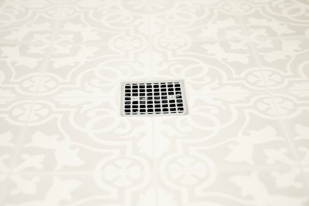 Closeup of white and grey patterned bathroom floor tiles with a chrome square grille shower drain in the middle.