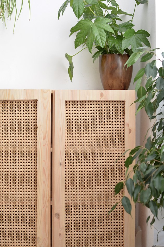 Plywood cabinet with cane paneling in a white room with vined potted plant resting on top of cabinet