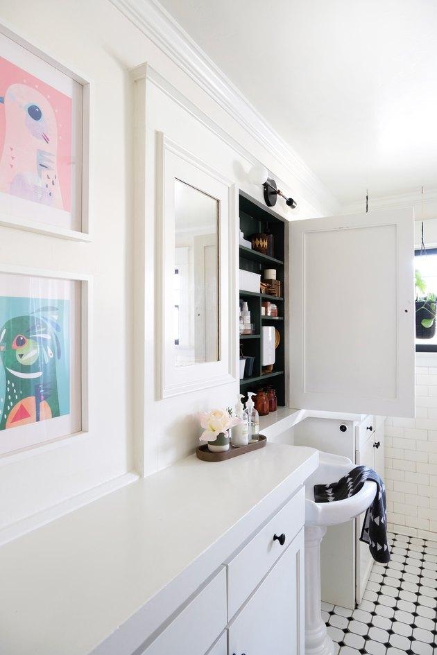 Salle de bain aux murs blancs avec carrelage noir et blanc