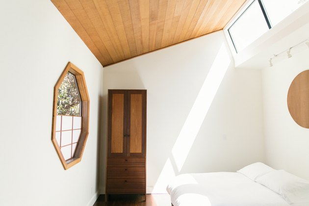 rustic decor in room with light wood paneled ceiling, arched ceiling, skylights, octagon window with panes and wood frame, white bedding, wood armoire.