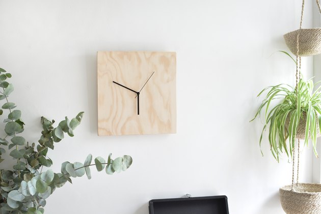 a clock with an unfinished plywood face mounted on a plain white wall