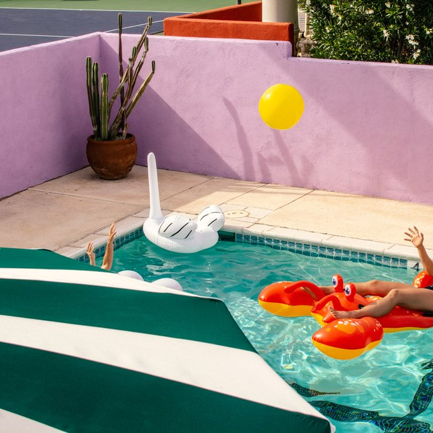Exterior swimming pool with lobster and swan inflatables with green and white umbrella, pink-painted brick wall, and yellow balloon