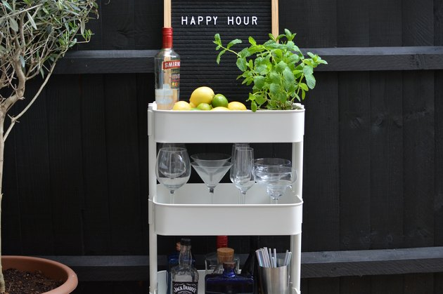 White bar cart with liquor bottles, glasses, and plant