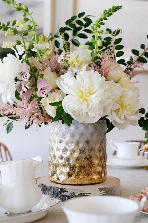 Vase texturé blanc or avec fleurs blanches et roses avec feuillage sur table à manger