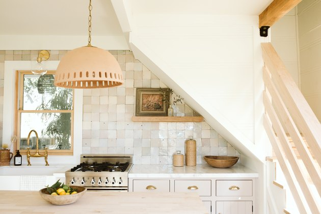 pendant lamp over wooden kitchen island in kitchen with beige tiled backsplash