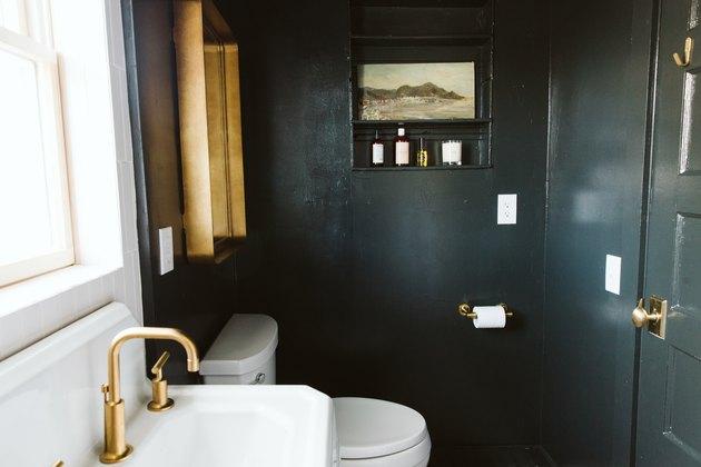 small bathroom wall art on black walls near mirror with brass frame