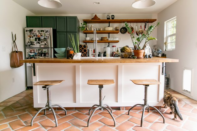 2021 kitchen color trend with white kitchen island with terra cotta floor and forest green cabinets