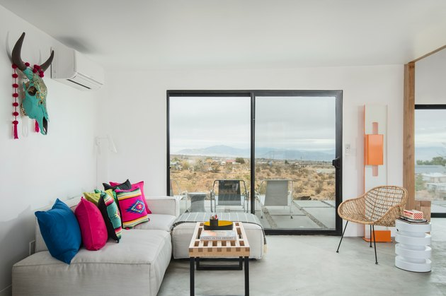 Minimal desert-inspired living room with light gray couch and neon geometric throw pillows