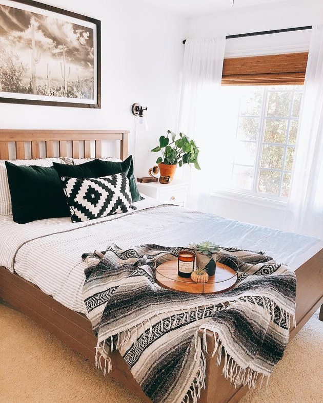 Minimal southwestern-inspired bedroom with black and white mexican blanket and dark green velvet throws on white bedding