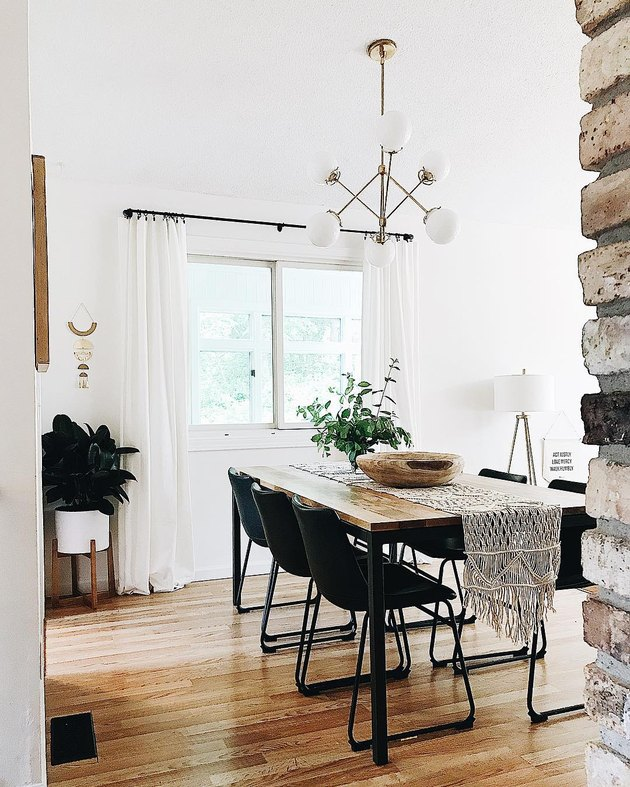 Minimal dining room with metal and wood table and black leather industrial chairs, white globe chandelier, and white midcentury floor planter