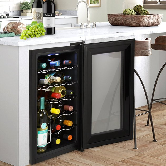 This is a single-zone cooler that keeps all 18 of your bottles within the temperature range of 54 – 64 degrees Fahrenheit using a thermoelectric cooling system. The freestanding design can accommodate floor, table or countertop placement, and measures 25 inches tall. It's also framed in a wide aluminum bezel and has interior LED lighting to illuminate your wine collection.